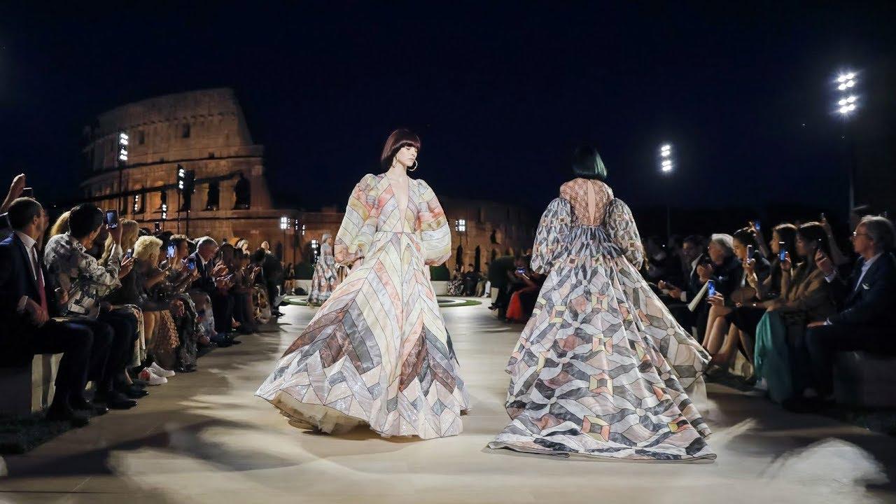 """След Седмицата на висшата мода в Париж през юли, модните поклонници се преместиха в Рим, където се състоя стилната екстраваганца на Fendi в памет на дизайнера Карл Лагерфелд. Сред звездните гости на дефилето около Колизеума бяха Катрин Зита-Джоунс и дъщеря й Карис, Джейсън Момоа, Сюзън Сарандън и много други. За шоуто Силвия Вентурини Фенди пренесе гостите си във Вечния град, за да представи кутюрна линия наречена """"Зората на романството"""", която включва общо 54 образа - в памет на 54-те години, които Лагерфелд е посветил на марката."""