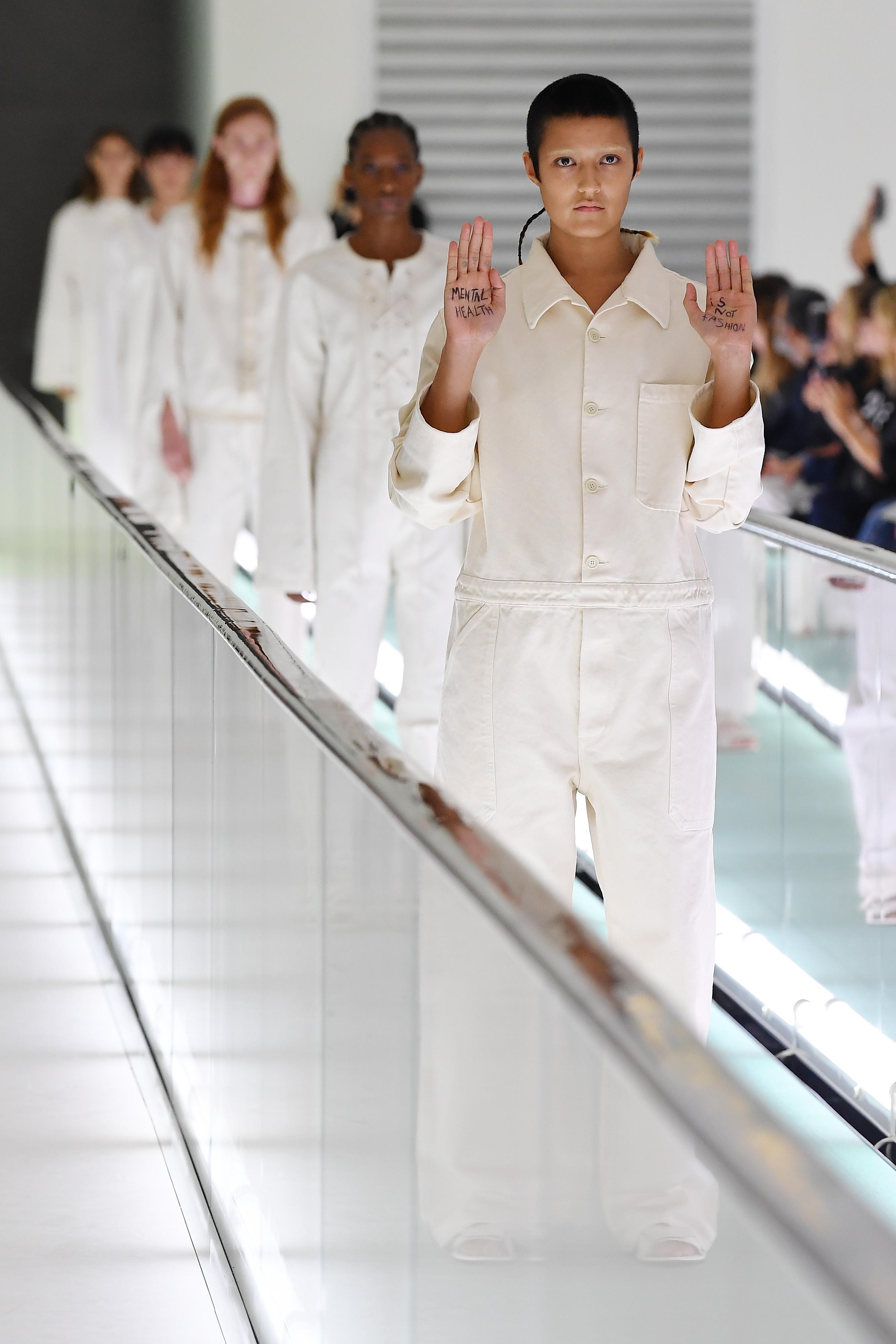 """Gucci презентацията за Пролет/Лято 2020 на Алесандро Микеле  възбужда разпалена дискусия по следната тема - идилията на """"болничното"""" начало на шоуто, прекъснато от мирния протест на един от моделите - директно от подиума. На 26-годишния модел Айеша Тан-Джоунс е отредено да дефилира с една от белите ризи в първата част на презентацията - докато е на сцената, Айеша вдига ръцете си на нивото на торса, а върху дланите й се чете: MENTAL HEALTH IS NOT FASHION, в знак на протест. Посланието има за цел да изрази негодуванието на модела срещу обидната употреба на усмирителни ризи."""