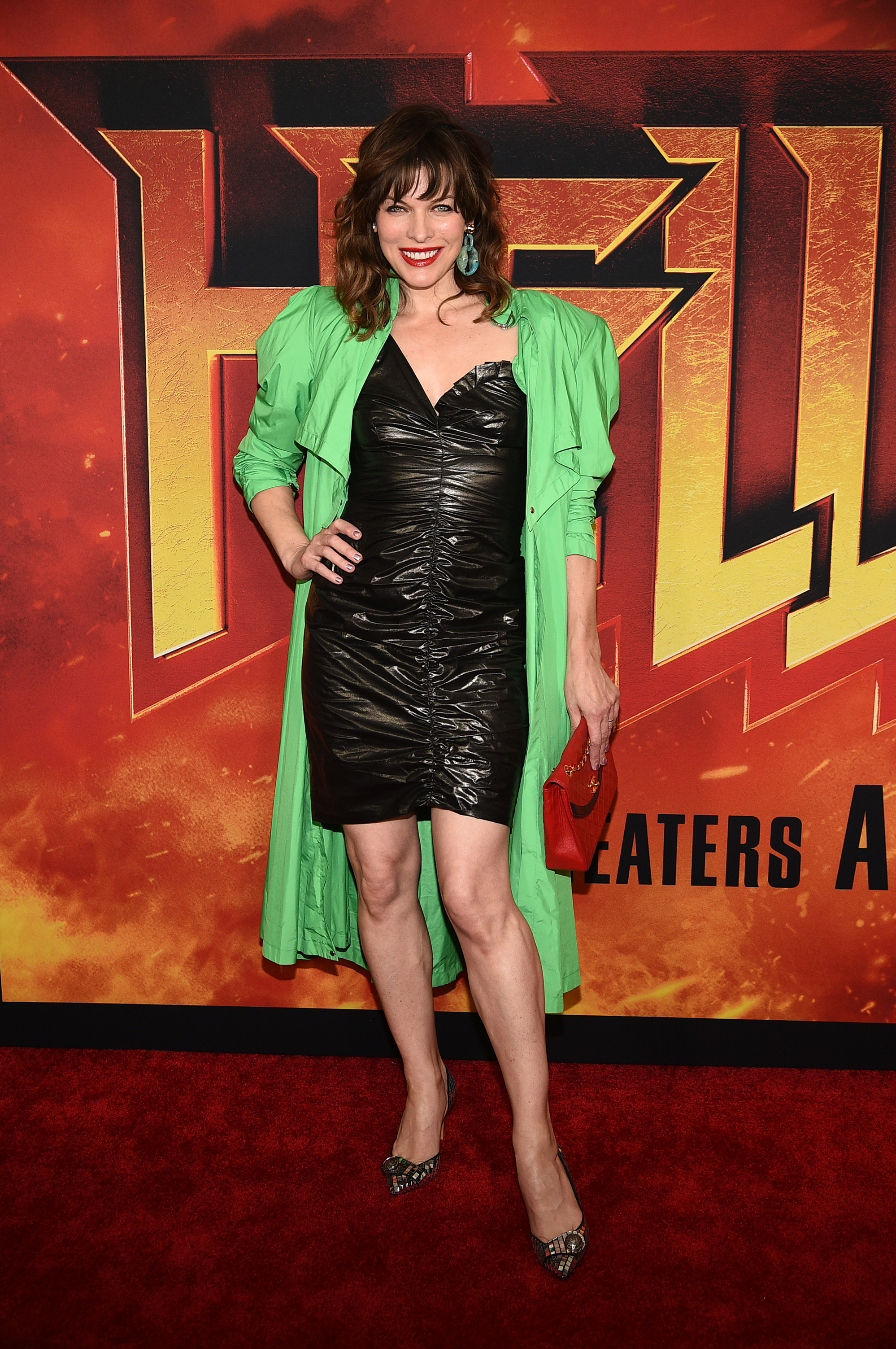 Набраната мини латексова рокля с едно рамо, неонов зелен тренч и червен клъч на Chanel са стилистичните  избори на  Мила Йовович, която реши да комбинира привидно несъчетаващи се модни елементи във визия за червен килим за премиерата на Hellboy на 9-ти април в Ню Йорк.