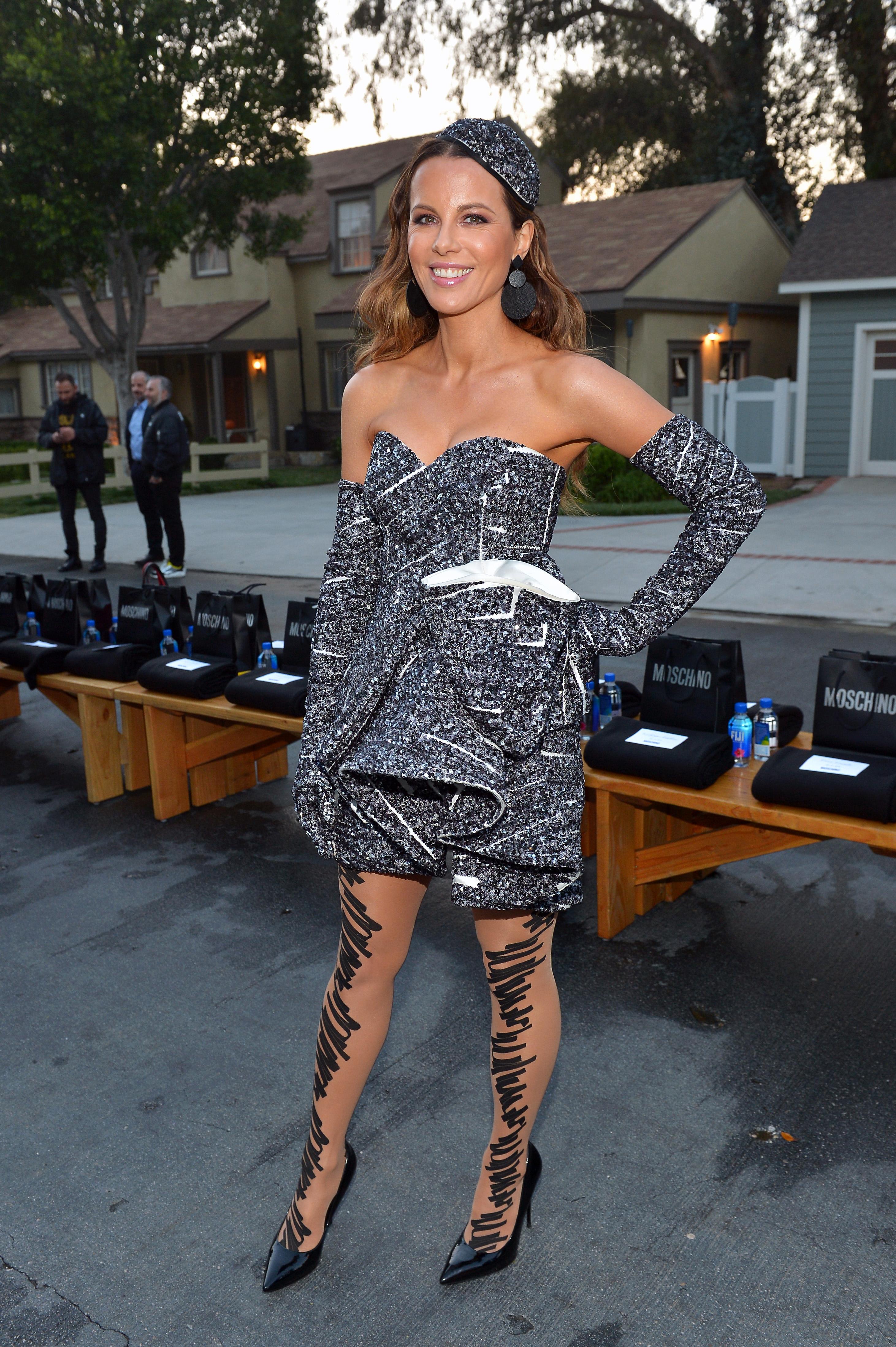 Колекцията Resort 2020  на Moschino в Лос Анджелис събра тълпа от фенове, сред които Кейт Бекинсейл, Парис Джексън, Рита Ора & more... За дефилето 45-годишната Кейт Бекинсейл, която скъса с 25-годишния си приятел Пит преди няколко месеца, се появи в черно-бяла мини рокля, избродирана със стотици пайети, създадена от Скот за колекцията, която дизайнерът посвети на дизайнерското студио, в което вечно вилнее хаос.