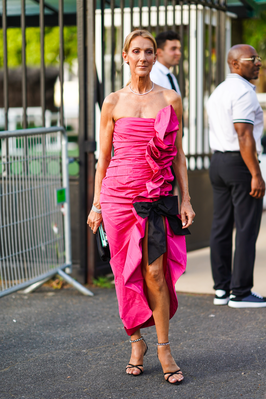 Miu Miu За да види круизната колекция Miu Miu, певицата избра рокля дело на Миуча Прада. Селин нямаше да е Дион, ако не бе принудила обществеността отново да говори за облеклото и тази вечер: сочна фуксия, много плътно деколте и перфектната нарязана рокля с драперии и голяма черна панделка - визия ясно видима и отдалеч.