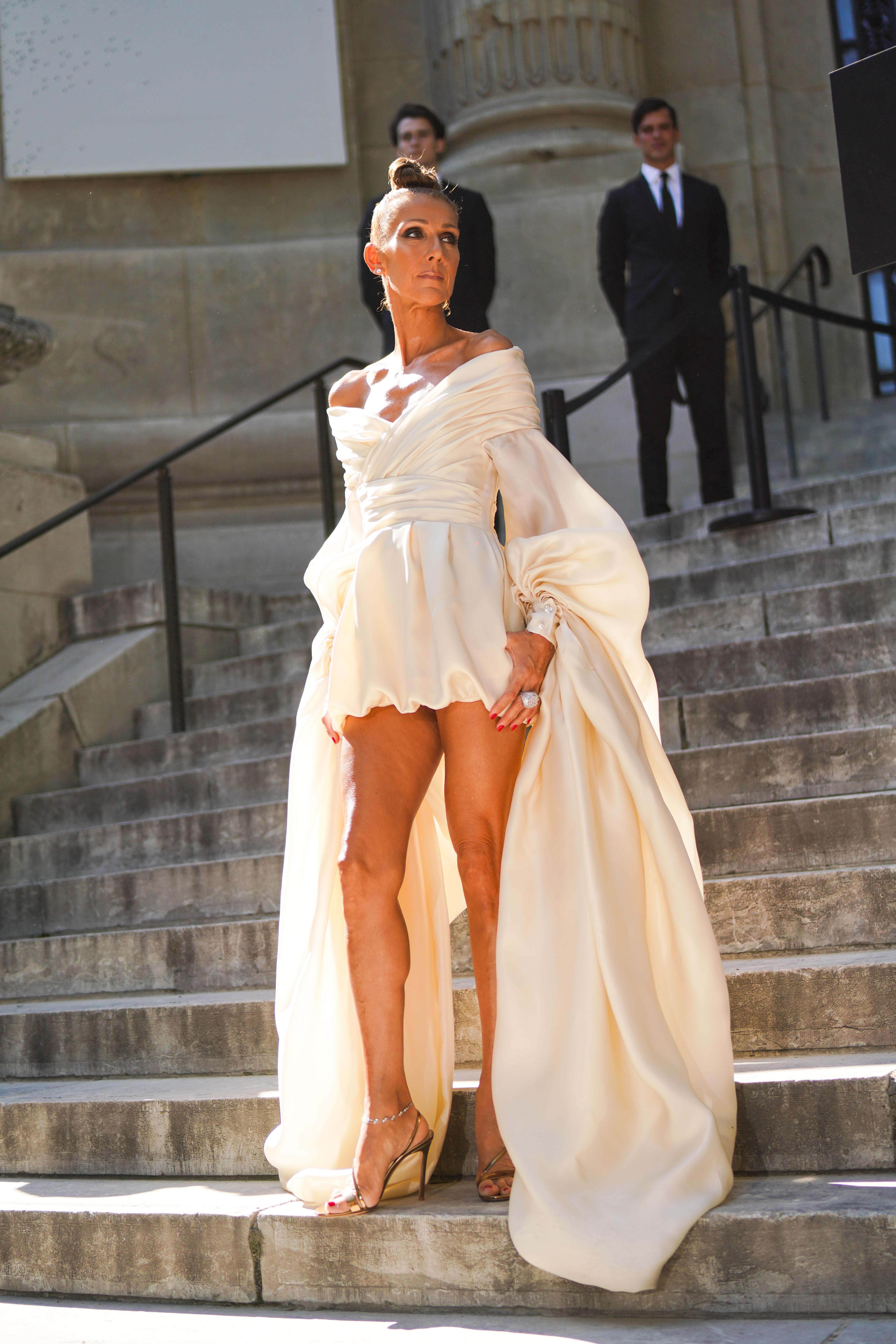 Alexandre Vauthier Преди старта на поредното дефиле, Селин успя да покаже чудесата на трансформацията на вечерната рокля на Александър Вотие от колекцията Пролет/Лято. На пръв поглед изглеждаше, че кремавият сатенен дизайн с голи рамене е дълга рокля, но когато Селин разпери ръце, една прекрасна мини-рокля се появи под дълги буфан ръкави. Златни лаконични сандали, минималистични обици и няколко закачливи пръстена с големи камъни завършиха визията на Дион.