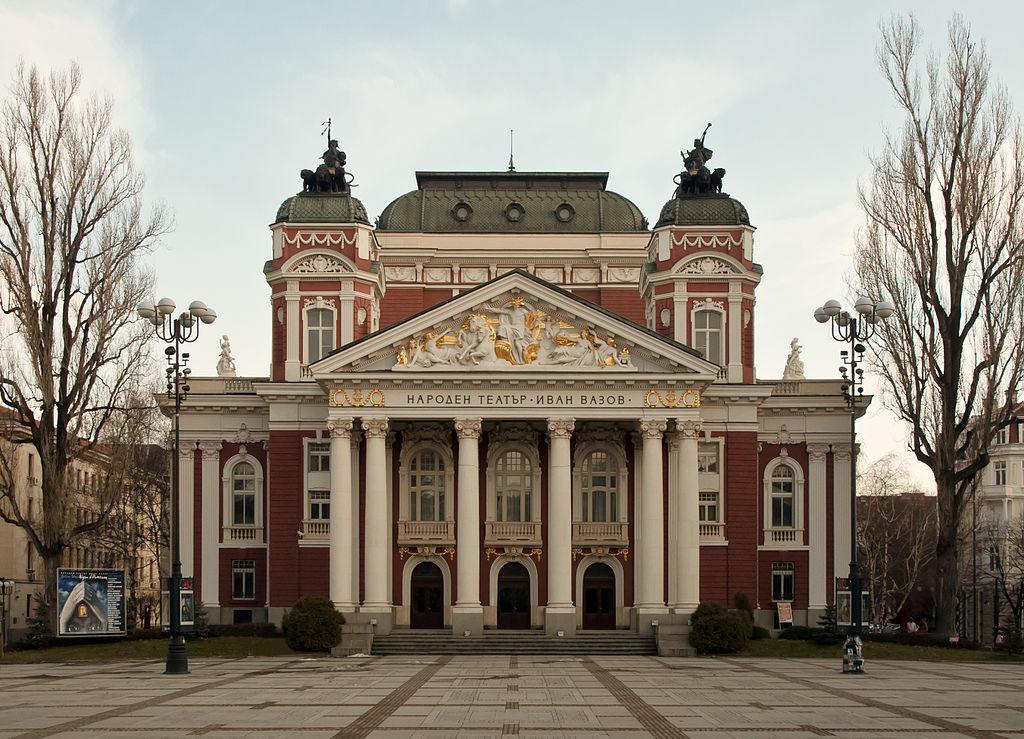 """Актьорската трупа на НТ Иван Вазов  снимка: Wikipedia Народен театър """"Иван Вазов"""" винаги се е смятал за постулат на културата, етикета и интелекта. Вярваме, че под покрива му наистина се случват чудеса, въпреки времето, в което живеем. Затова и никак случайно трупата от актьори влиза в списъка ни с """"модерни будители - творители"""", които ни карат сериозно да се замислим. Пренасят на сцените на театъра векове история, напластявания и преживявания и правят нас, публиката, съпричастни с изживяването, което представлява театралното изкуство."""