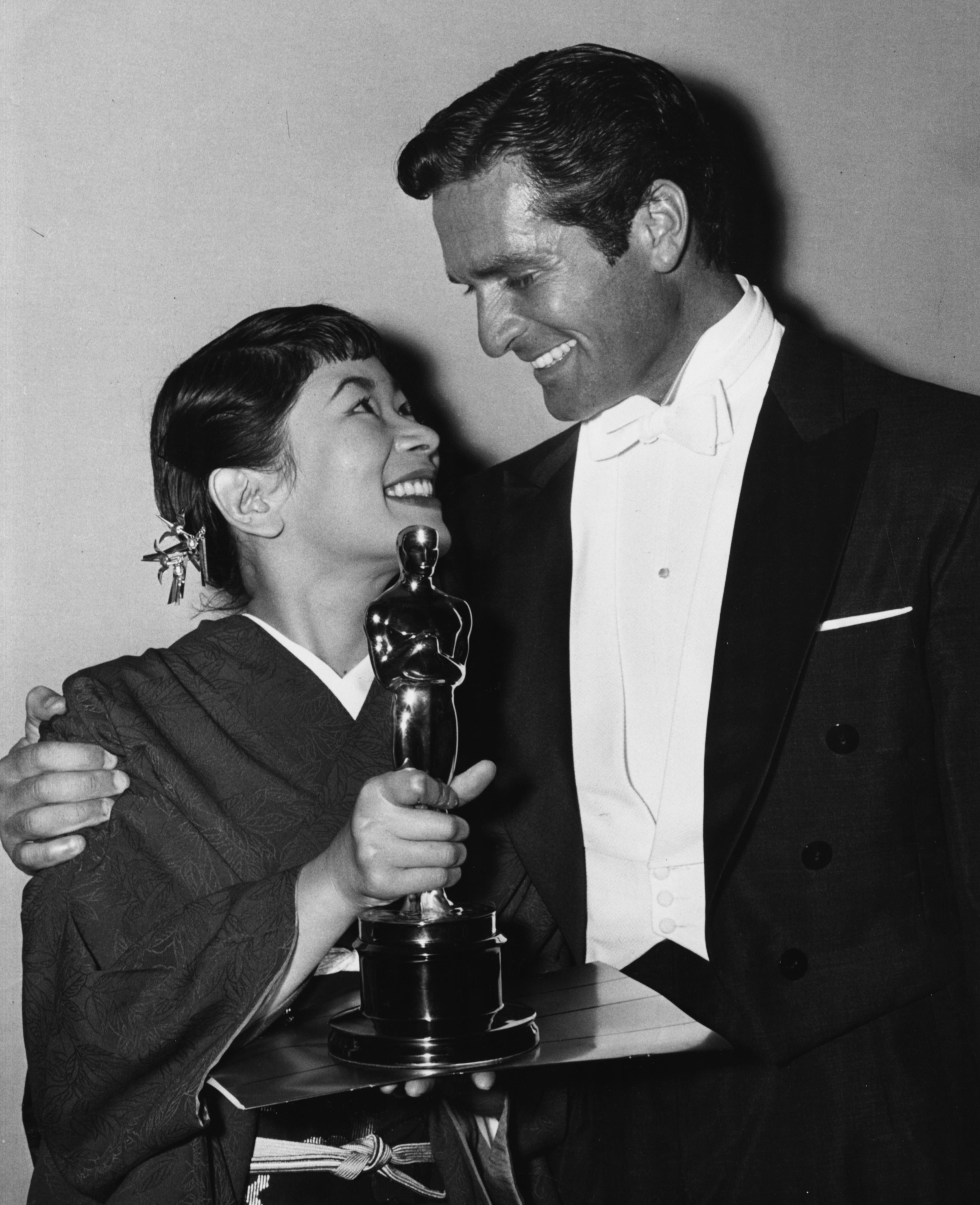 Мийоши Умеки държи Оскар за Най-добра поддържаща женска роля в Sayonara. До нея стои Хю О'Брайън, 1958