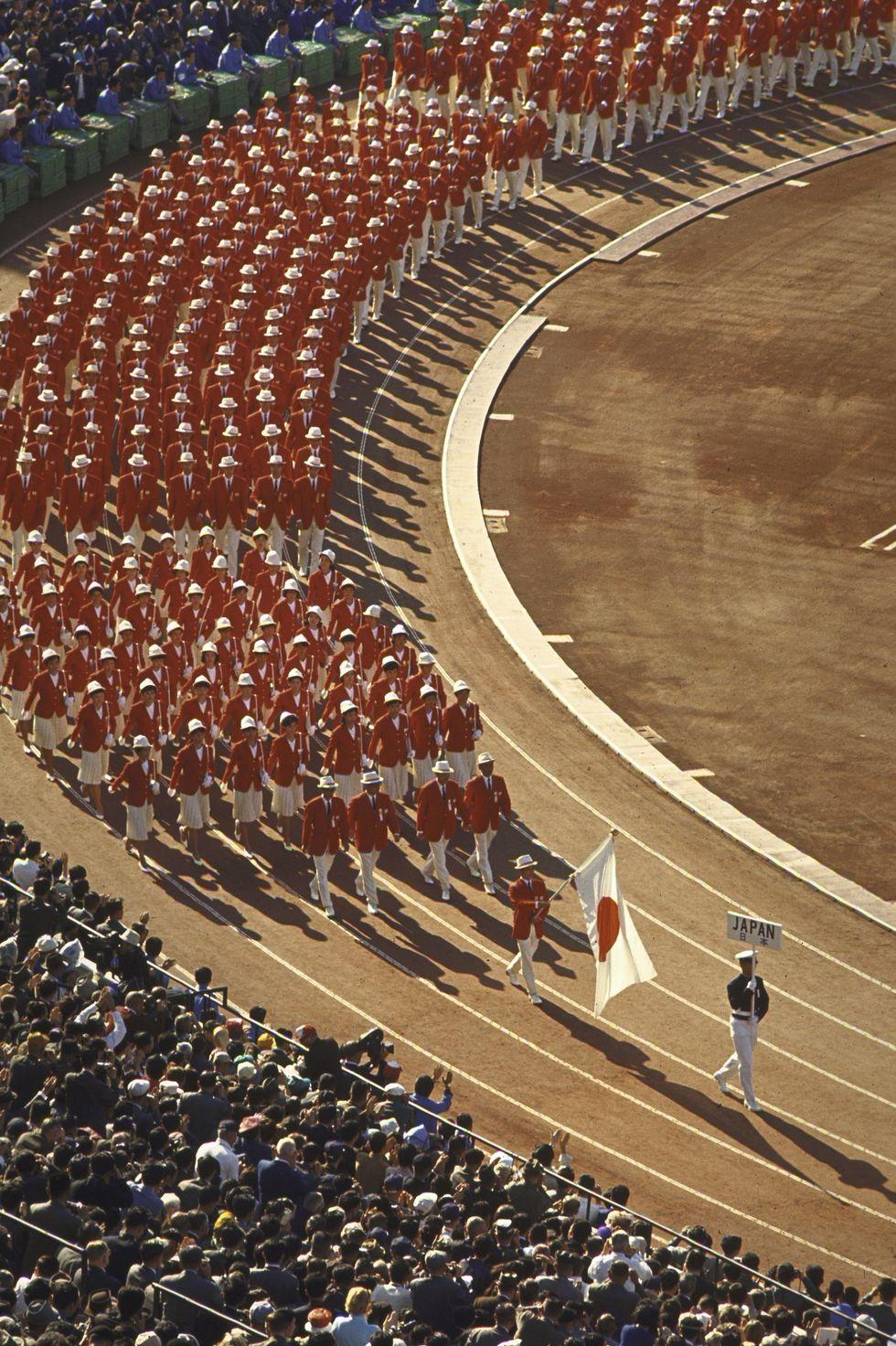 1964: Олимпийците на Япония На откриването през 64-та японските спортисти не остават незабелязани, когато пристигат в цветовете на знамето си - бели панталони и червени блейзъри за всички.