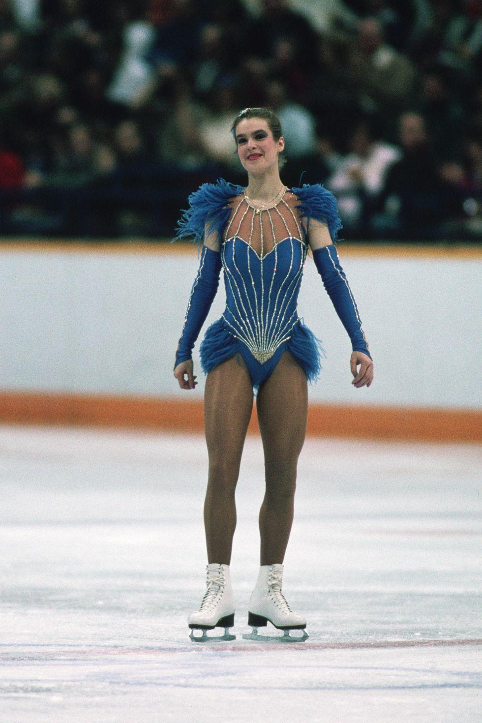 """1988: Катарина Вит 4 години по-късно Уит отново главозамайва с тоалет - трико с пера и блестящи елементи. Липсата на пола обаче разклаща федерацията, която скоро измисля """"Правилото Катарина"""", задължаващо всички фигуристки да носят поли. Спорът не наранява спортиската и тя успешно се пързаля към поредната златна победа."""