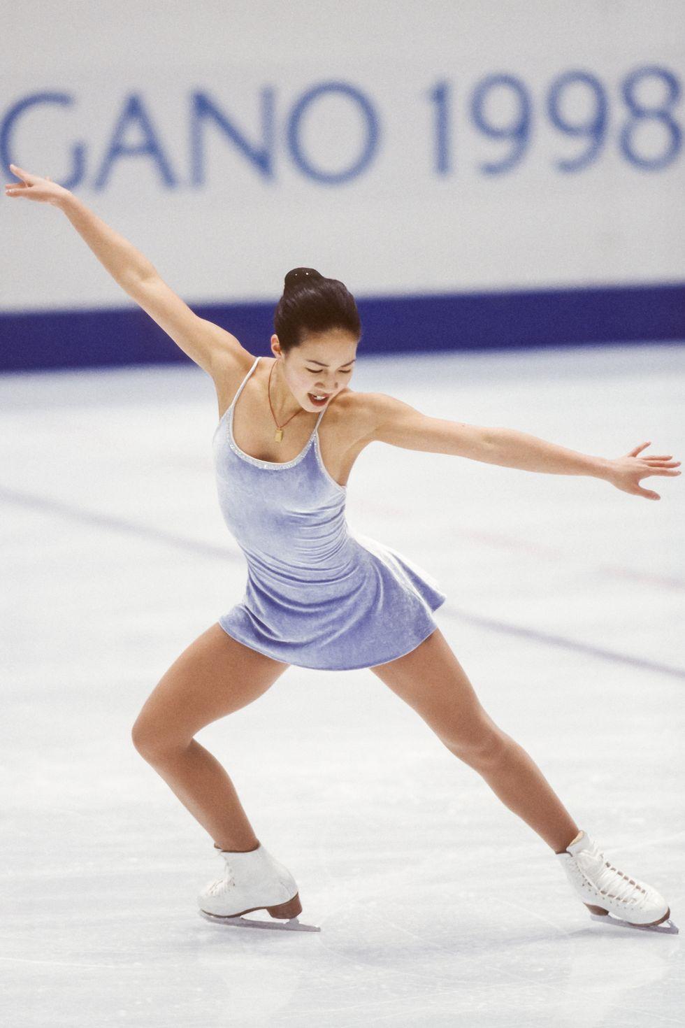 """1998: Мишел Куан Вера Уанг отново остава отпечатък в спорта, създавайки роклята на Мишел Куан за Зимната Олимпиада в Япония. """"Предпочитах нещо семпло и елегантно, за да не се разсейват красотата на движенията на леда,"""" казва Куан в интервю през 2017."""