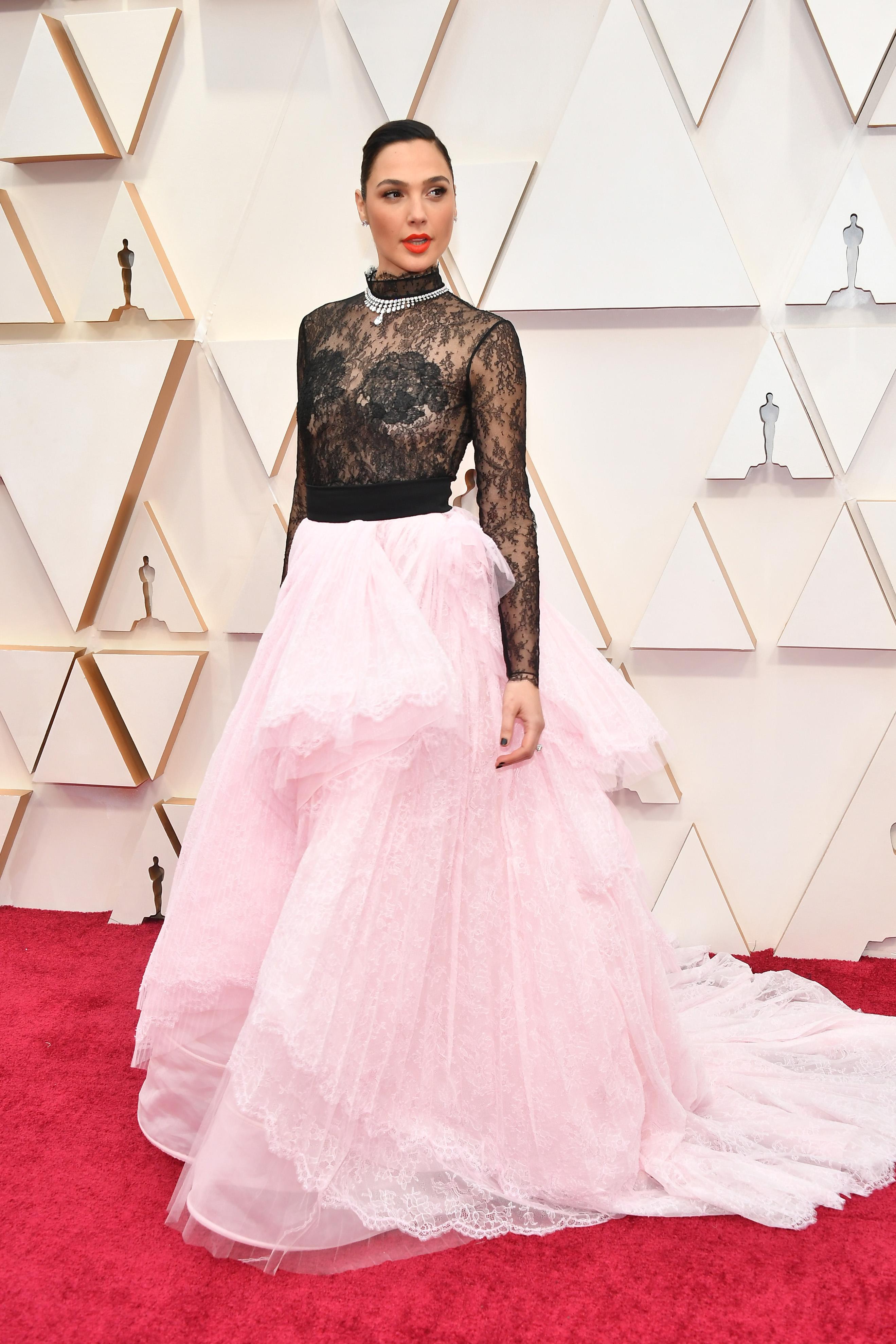 Гал Гадот в Givenchy Визията на актрисата изглежда по-скоро като подигравка, отколкото като дизайнерско решение, което ще остане неразбрано. Голямата розова пола, пристегната в талията с колан, дантеленото боди с по-едра дантела около бюста, както и голямото диамантено колие над него, са все елементи, които не бива да се съчетават заедно.